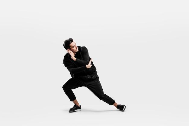 スタイリッシュな黒い服を着たハンサムなダンサーがストリートダンスを踊っています