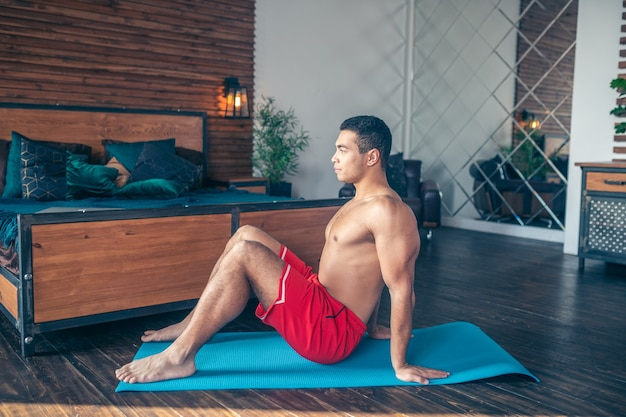 Handsome dark-haired man in red shorts sitting on blue mat