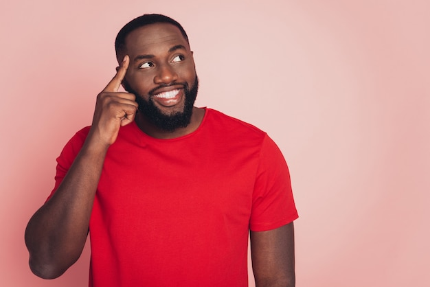 Handsome dark skin guy thinking looking aside copy-space isolated over pink background
