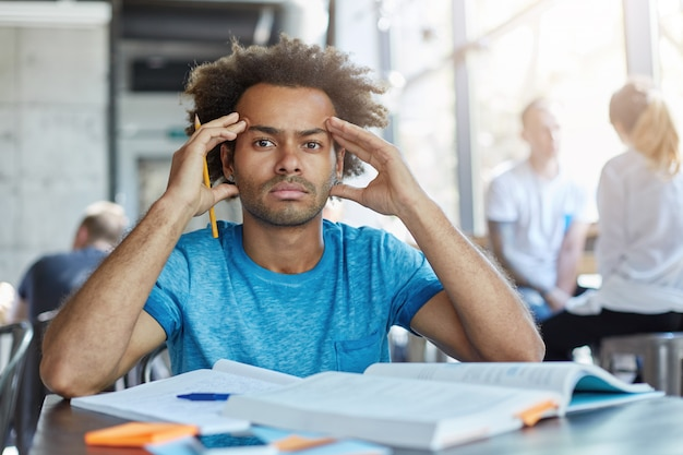 Handsome dark-skinned bearded student with afro haircut squeezing temples, having headache while preparing for exams or tests night and day, looking with painful frustrated expression