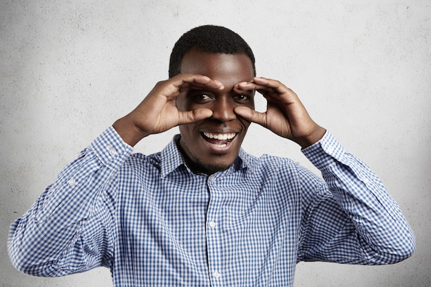 Handsome dark-skinned employee wearing checkered shirt holding his hands at his eyes as if looking through binoculars or glasses, smiling happily agains  wall