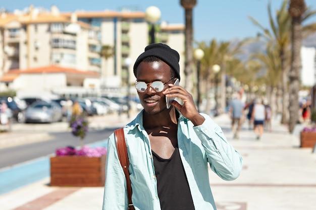 トレンディな帽子とサングラスでハンサムな黒肌のファッショナブルな男が携帯電話で話し、大都市を歩き回り、彼の前に美しい女性を見ているので立ち止まった