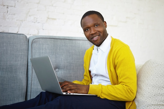 Красивый темнокожий блоггер в желтом кардигане за клавиатурой на обычном портативном компьютере публикует новый пост в своем онлайн-блоге, вдохновляет на выражение, смотрит и улыбается