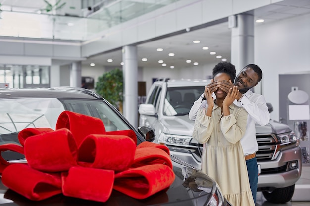 Handsome dark-skinned man pleases his wife in dealership
