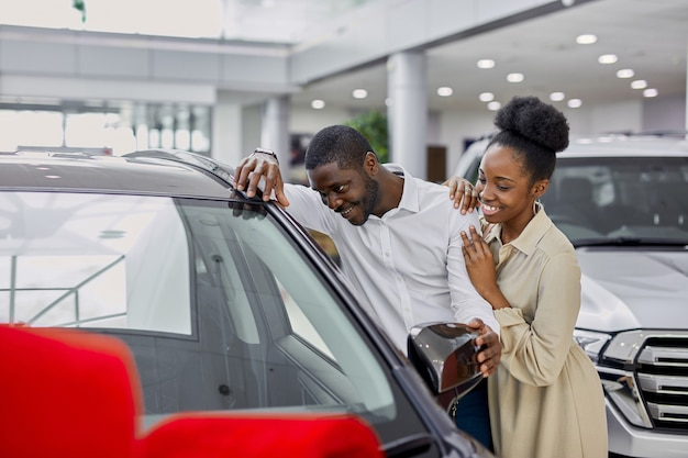Красивый темнокожий мужчина ублажает жену в автосалоне