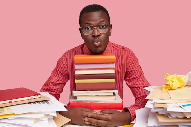 잘 생긴 어두운 피부를 가진 남자는 입술을 삐고, 책 더미를 들고, 바탕 화면에 엉망이 있고, 안경과 줄무늬 셔츠를 입는다.