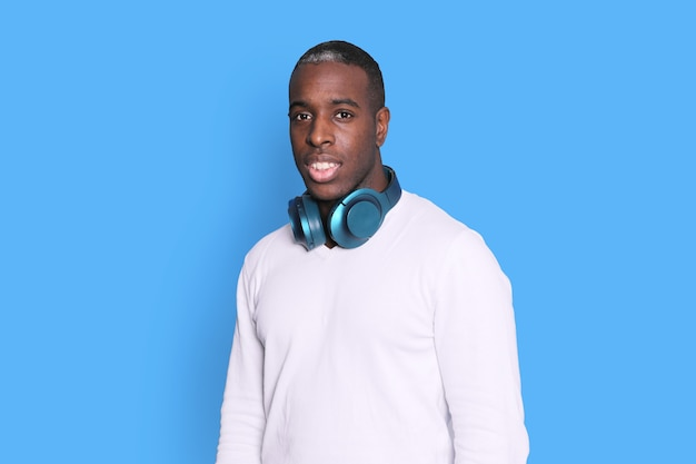 Handsome dark skinned man with headphones around his neck while looking camera against blue background
