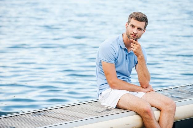 Красивый мечтатель. задумчивый молодой человек, взявшись за подбородок и глядя в сторону, сидя на берегу реки