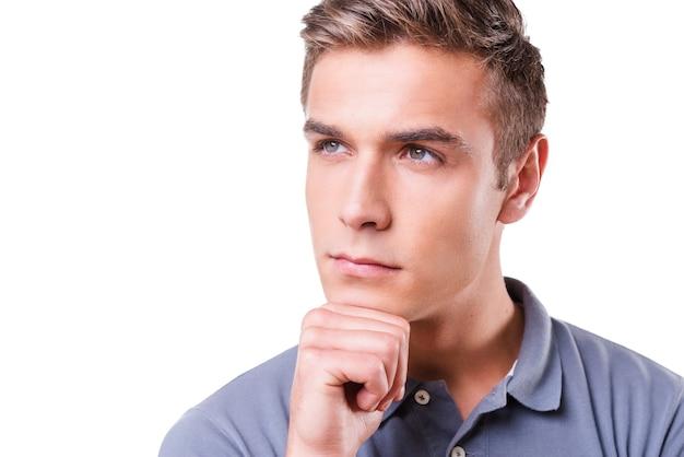 Красивый мечтатель. вдумчивый молодой человек держит руку на подбородке и смотрит в сторону, стоя изолированно на белом фоне