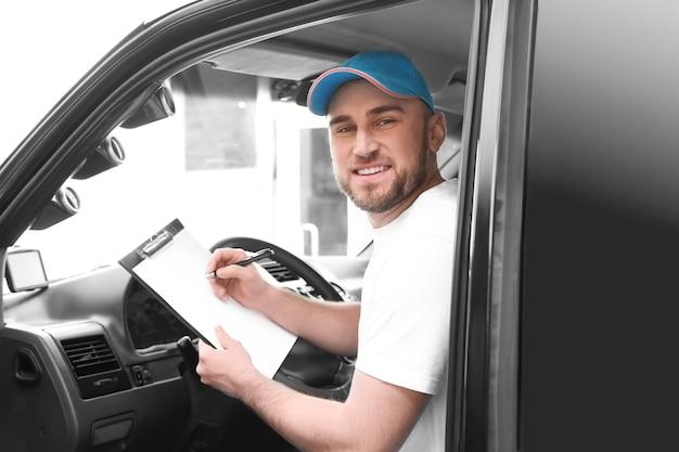 Красивый доставщик, сидящий в машине