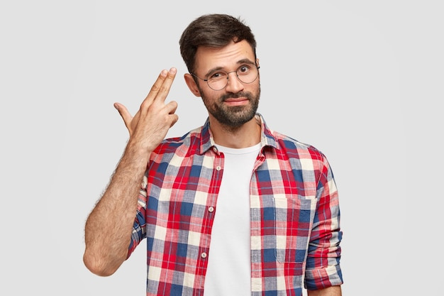 Handsome displeased bearded guy being fed up with everyday life, makes suicide gesture
