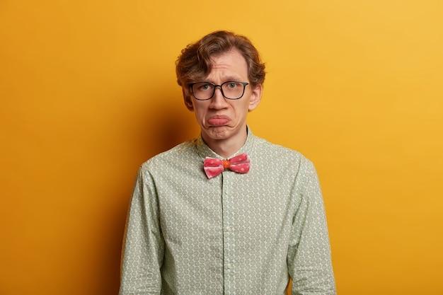 잘 생긴 고민 된 남자는 무언가에 불만족스러운 입술을 꽉 쥐고, 불행한 하루를 보내고, 광학 안경과 정장 셔츠를 입고, 노란색 벽에 포즈를 취합니다. 부정적인 얼굴 표현 개념.