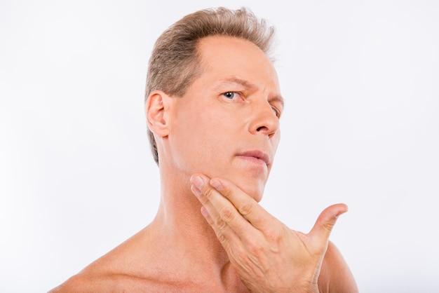 Handsome disturbed aged man touching his face after shave