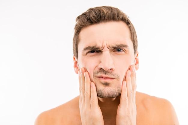Красивый встревоженный молодой человек трогает его лицо после бритья