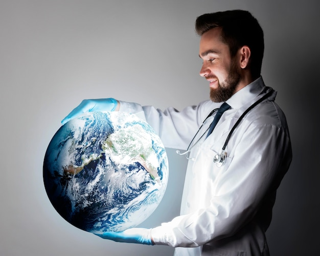 Handsome doctor holding globe representing the world