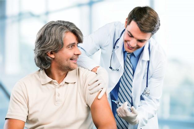 Красивый врач делает вакцинацию пациенту мужского пола на фоне