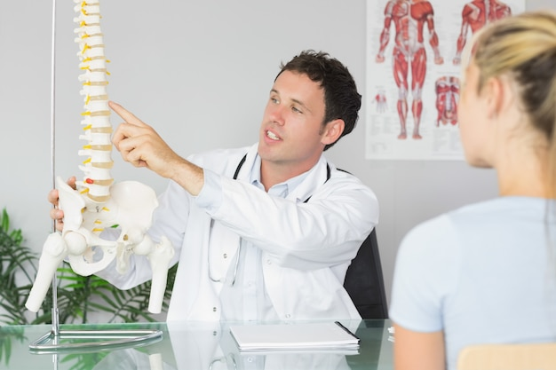 Handsome doctor showing a patient something on skeleton model