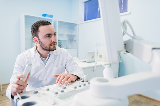 Handsome doctor using an ultrasound machine