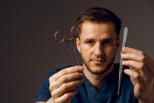 外科用はさみと持針器を持つハンサムな医者。医療機器を手に持っている自信のある人。
