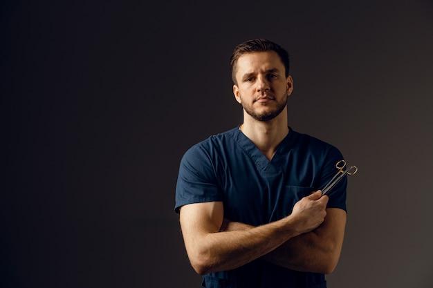 外科用はさみを持つハンサムな医者。医療機器を手に持って笑顔で自信を持って男。
