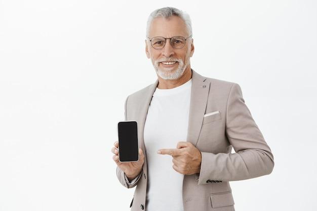 휴대 전화 화면에서 가리키는 소송에서 잘 생긴 노인 수염 된 사업가