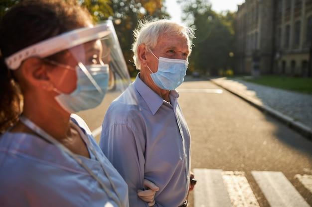 보호 마스크를 쓴 잘생긴 노인은 도시에서 의료 종사자와 시간을 보낸다