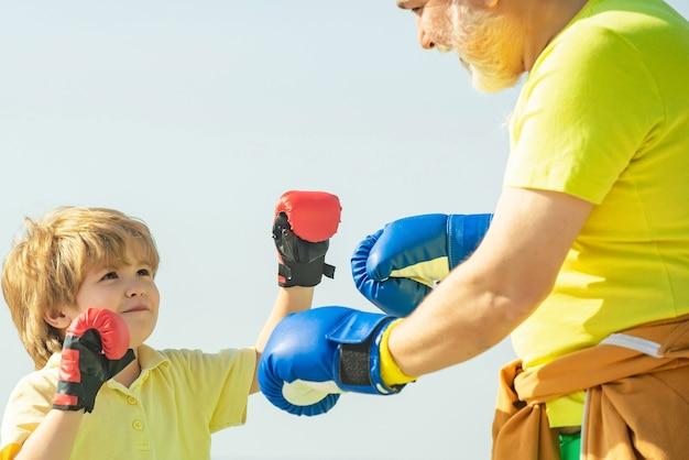 Красивый пожилой мужчина упражнениями по боксу. пожилой мужчина ударяет боксерскую грушу. дед и