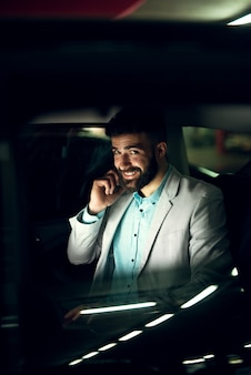 ハンサムなエレガントなビジネスマンが携帯電話で話しながら車の窓から見ています。