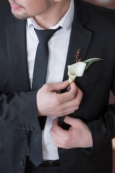 Handsome elegant groom in black wedding tuxedo with white shirt