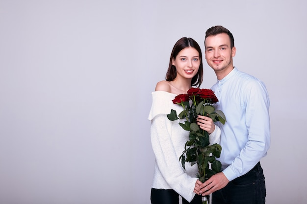 Handsome elegant guy gives roses to his beautiful womanfriend.