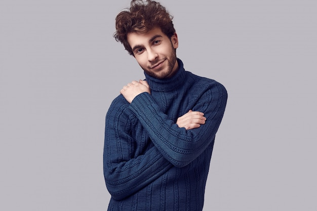 Handsome elegant man with curly hair in blue sweater