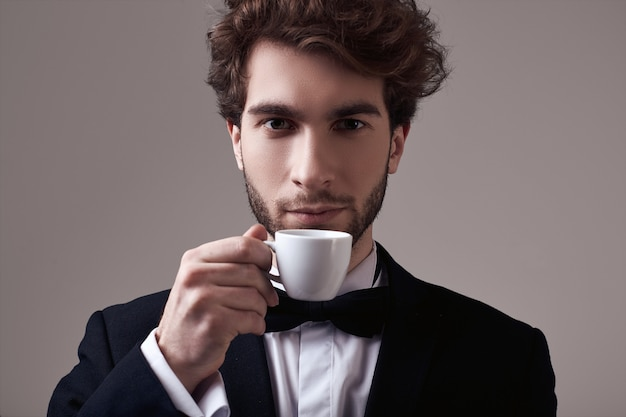Handsome elegant man with curly hair in tuxedo holding a cup of espresso
