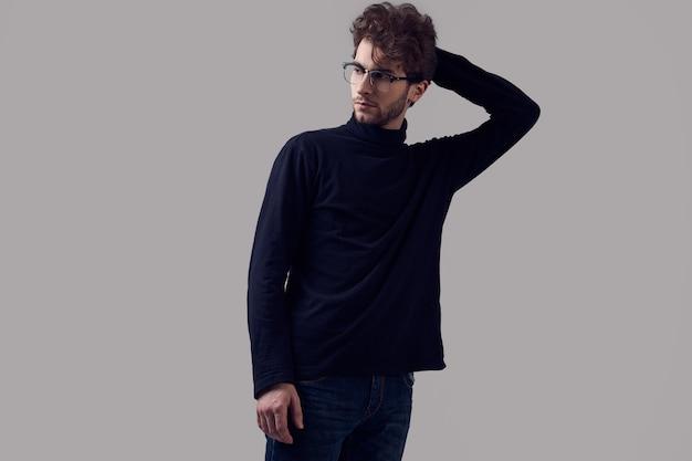 Красивый элегантный мужчина с вьющимися волосами в черной водолазке и очках