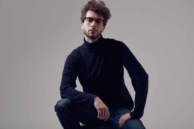 Handsome elegant man with curly hair wearing black turtleneck and glasses