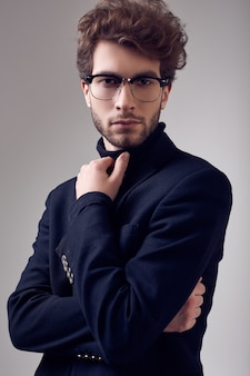 Handsome elegant man with curly hair wearing suit and glasses