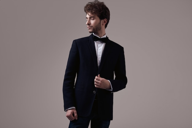 Handsome elegant man with curly hair wearing tuxedo