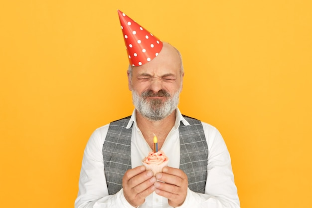 Красивый элегантный старший мужчина с густой седой бородой в шляпе-конусе закрывает глаза, загадывая желание