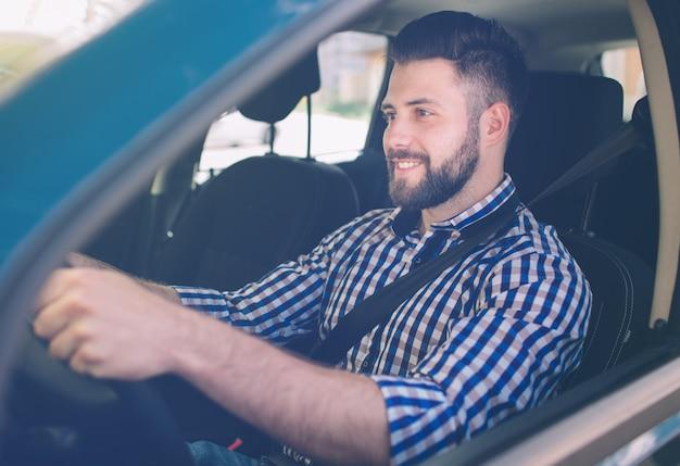 Handsome elegant serious man drives a car.