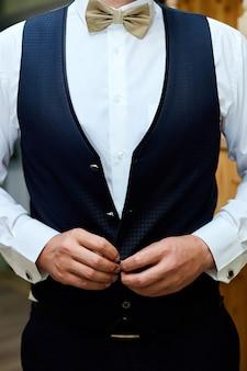 古典的な衣装のスーツと蝶ネクタイのハンサムなエレガントな若いファッション男