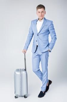 スーツケースと立っている青いスーツのハンサムなエレガントな若い男