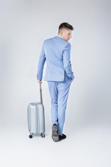 Красивый элегантный молодой человек в синем костюме стоит спиной с чемоданом