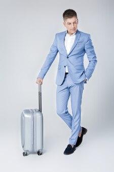 スーツケースを持って歩く青いスーツのハンサムなエレガントな若い男