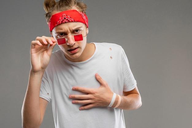 Красивый эмоциональный мальчик-подросток позирует в студии на сером, парень в серой футболке и красных очках морщится на себя
