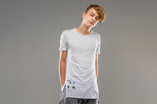 Handsome emotional teenager boy posing in studio against gray, young man in a light t-shirt, mockup