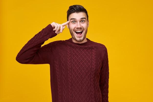 Красивый эмоциональный молодой мужчина выражает сумасшедшие эмоции, держа указательный палец возле головы. возбужденный парень в вязаном джемпере катит пальцем у виска, широко открывая рот. подумайте, прежде чем действовать