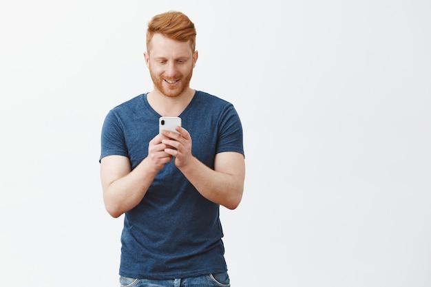 Maschio rosso emotivo bello in abbigliamento casual, guardando lo schermo del cellulare durante la digitazione del messaggio sul muro grigio