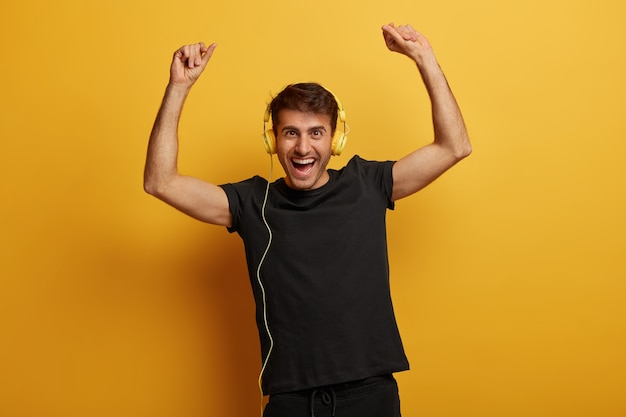 Handsome energetic man raises arms with happiness, wears headset, sings along with favorite song, dressed in black t shirt, has overjoyed expression, isolated over yellow background