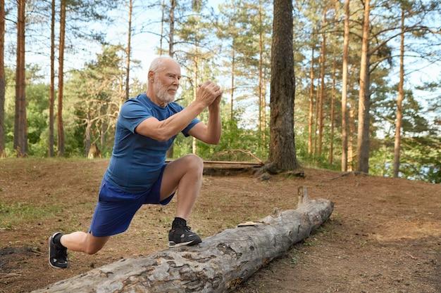 野生の自然の中で有酸素運動をしているスポーツ服を着ているひげを持つハンサムなエネルギッシュな年配の男性。走る前に足を丸太につけ、脚の筋肉を鍛える、うれしそうな自信に満ちた表情の老人