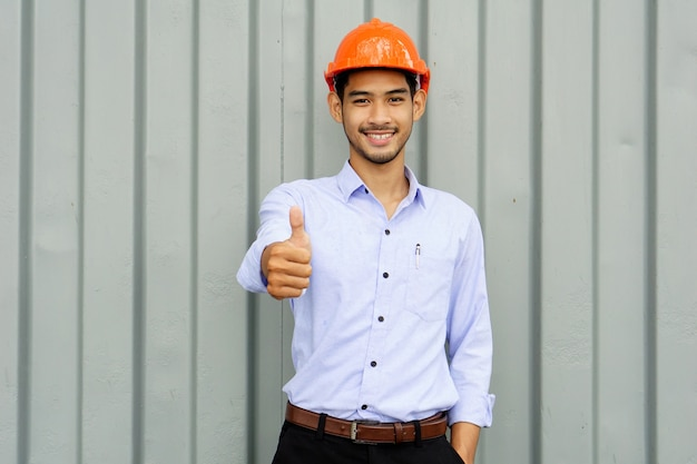 Handsome engineer wears orange safety helmet shows thumb up with smiling face