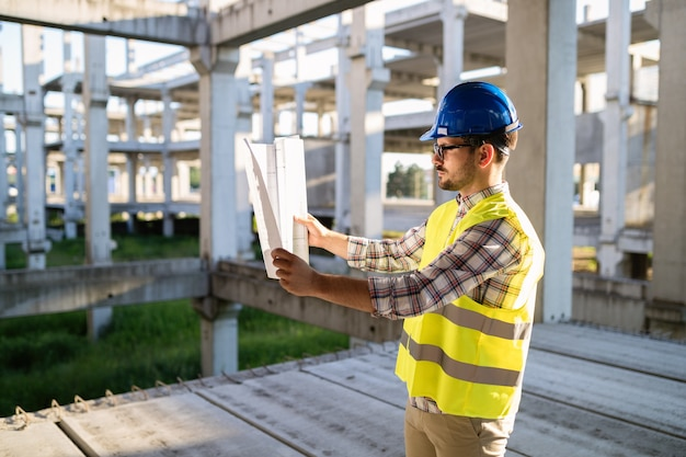 Handsome engineer working on construction site and holding blueprint